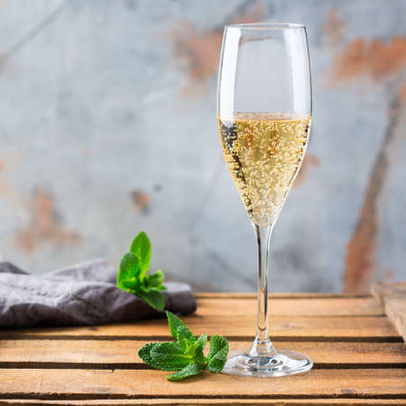 Photo for Food and drink, holidays party concept. Cold fresh alcohol beverage champagne sparkling white wine with bubbles in a flute glass on a wooden table. Copy space background - Royalty Free Image