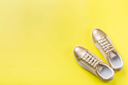 Photo pour Fashion, blog, blogging, lifestyle, well-being trendy concept. Pair of golden female sneakers on yellow background, top view, copy space, flat lay - image libre de droit