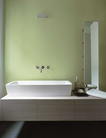 detail of washbasin in a modern bathroom with green wall
