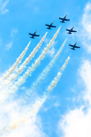 Foto de Group of fighter planes fly up with a smoke track against a blue sky with clouds - Imagen libre de derechos