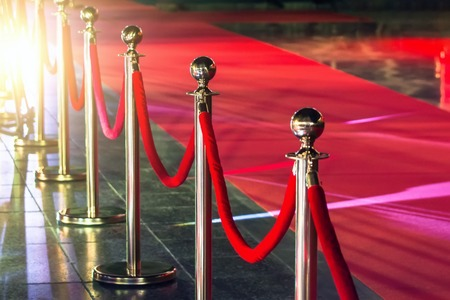 Foto per Portable Barrier for Queue Control. Red security rope by red carpet - Immagine Royalty Free