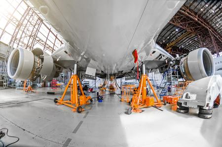 Foto de A large aircraft for service maintenance on special jacks in the hangar - Imagen libre de derechos