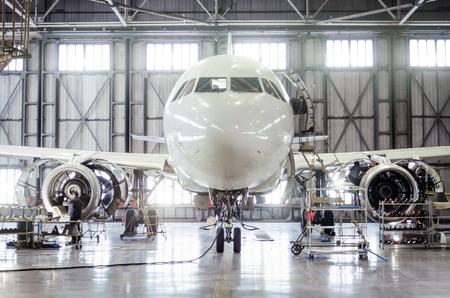 Foto de Passenger aircraft on maintenance of engine and fuselage repair in airport hangar - Imagen libre de derechos