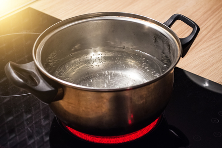 Foto de Metal pan with boiling water on the induction cooker red hot plate - Imagen libre de derechos