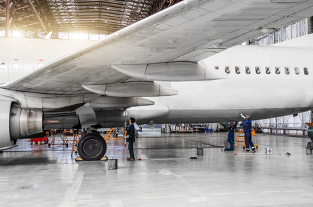 Photo for Several people wash the aircraft in the hangar for maintenance, view of the chassis, wing and tail - Royalty Free Image