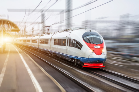 Foto per High speed train rides at high speed at the railway station in the city - Immagine Royalty Free