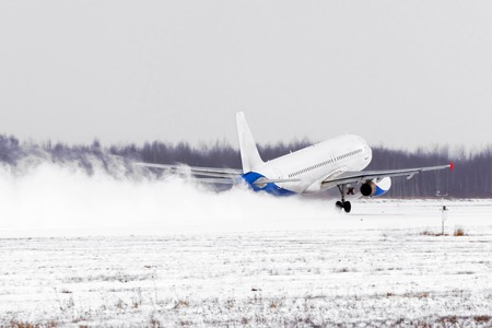 Foto de Airplane take off from the snow-covered runway airport in bad weather during a snow storm, a strong wind in the winter - Imagen libre de derechos