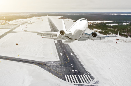 Foto de Airplane is climb flight level high view in the air, against the background of the winter airport of the runway, city, snow, forests and roads - Imagen libre de derechos