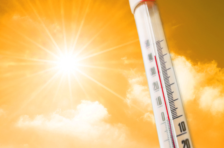 Foto de Thermometer against the background of an orange yellow hot glow of clouds and sun, concept of hot weather - Imagen libre de derechos