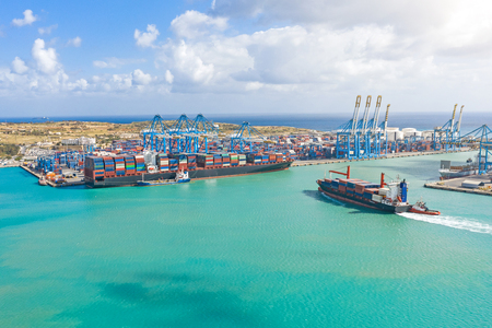 Foto de Aerial view from the height of a cargo harbor in a cargo seaport, a sailing ship with containers, and another one on the loading of goods - Imagen libre de derechos