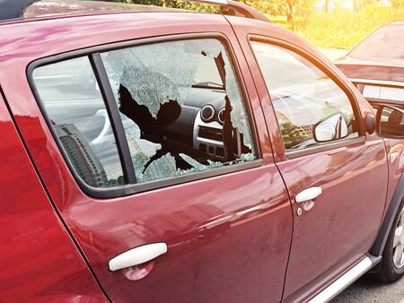 Foto de Broken glass on the passenger door of a passenger car parked. The concept of crime of car theft, theft of valuables - Imagen libre de derechos