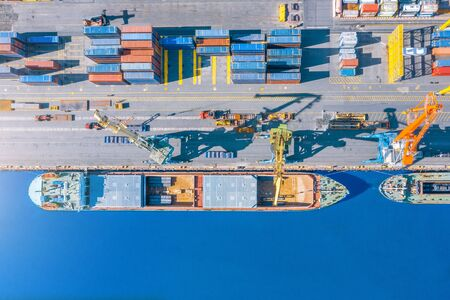 Foto de Aerial top view huge cargo ship moored at the pier at the port, loading goods, metal, concrete and other solid raw materials - Imagen libre de derechos