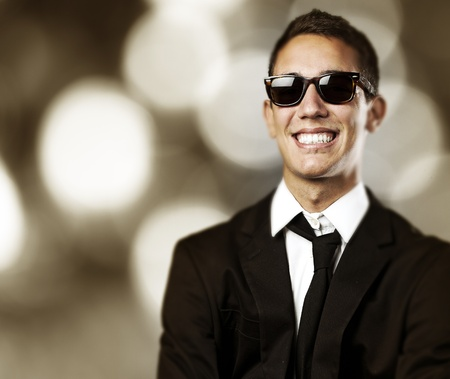 portrait of business man with sunglasses laughing against a abstract background