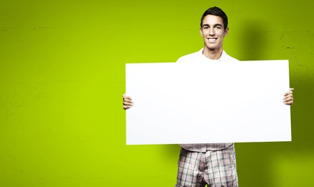 Photo for young man smiling and showing a big banner against a green background - Royalty Free Image