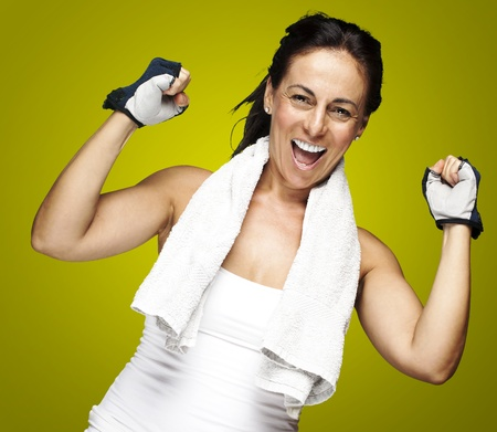 Photo for young sporty woman doing a winner gesture against a green background - Royalty Free Image