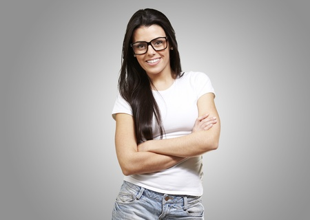 pretty young woman with glasses crossing her arms against a grey background