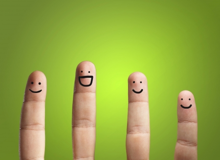 Photo pour Close-up Of Fingers With Smiley Face Isolated On Green Background - image libre de droit