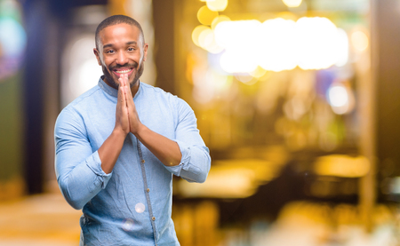 Foto de African american man with beard with hands together in praying gesture, expressing hope and please concept at night - Imagen libre de derechos