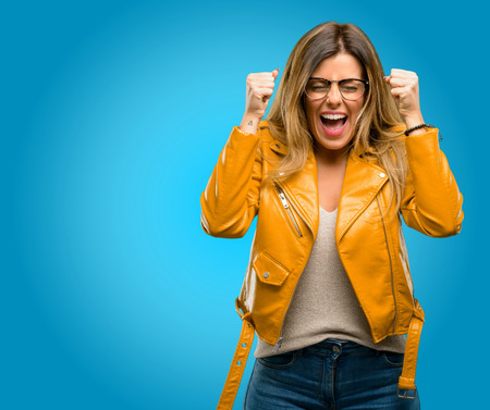 Photo for Beautiful young woman happy and surprised cheering expressing wow gesture, blue background - Royalty Free Image