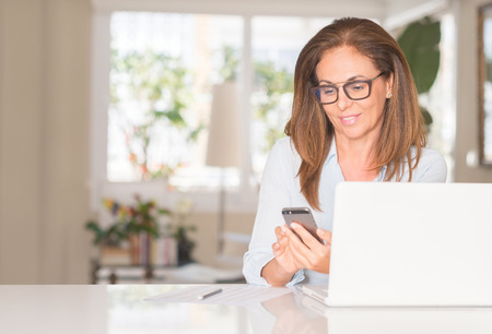 Photo for Middle age woman using smartphone and laptop, indoor - Royalty Free Image