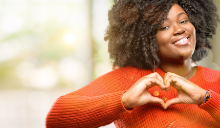 Photo for Beautiful african woman happy showing love with hands in heart shape expressing healthy and marriage symbol, outdoor - Royalty Free Image
