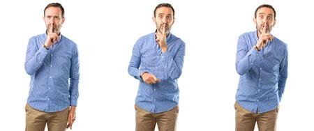 Foto de Middle age handsome man with index finger on lips, ask to be quiet. Silence and secret concept over white background - Imagen libre de derechos