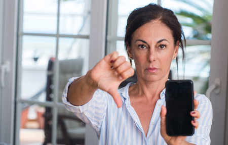 Photo pour Middle aged woman using smartphone with angry face, negative sign showing dislike with thumbs down, rejection concept - image libre de droit