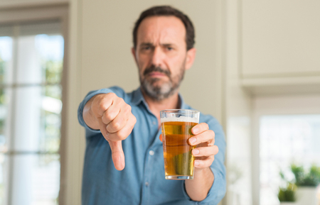 Foto de Middle age man drinking beer with angry face, negative sign showing dislike with thumbs down, rejection concept - Imagen libre de derechos