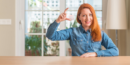 Photo for Redhead woman at home smiling and confident gesturing with hand doing size sign with fingers while looking and the camera. Measure concept. - Royalty Free Image