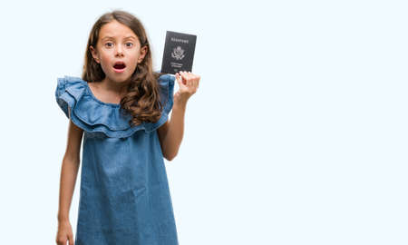 Photo for Brunette hispanic girl holding passport of United States of America scared in shock with a surprise face, afraid and excited with fear expression - Royalty Free Image