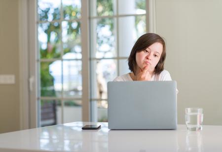 Foto de Down syndrome woman at home using computer laptop serious face thinking about question, very confused idea - Imagen libre de derechos