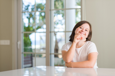 Foto de Down syndrome woman at home looking confident at the camera with smile with crossed arms and hand raised on chin. Thinking positive. - Imagen libre de derechos