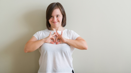 Foto de Down syndrome woman standing over wall smiling in love showing heart symbol and shape with hands. Romantic concept. - Imagen libre de derechos