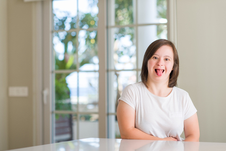Foto de Down syndrome woman at home sticking tongue out happy with funny expression. Emotion concept. - Imagen libre de derechos