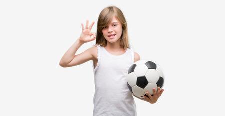 Foto de Young blonde toddler holding football ball doing ok sign with fingers, excellent symbol - Imagen libre de derechos