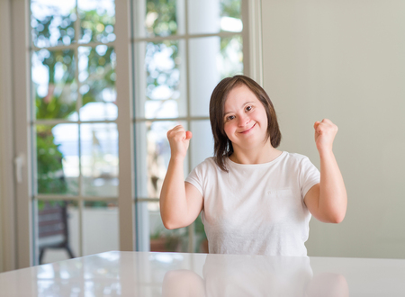 Foto de Down syndrome woman at home screaming proud and celebrating victory and success very excited, cheering emotion - Imagen libre de derechos