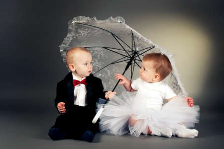 little boy and girl sitting under umbrella