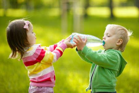 Photo pour Girl helps the boy to keep a bottle - image libre de droit