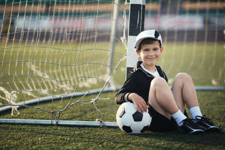 Photo for Little boy plays football on stadium - Royalty Free Image