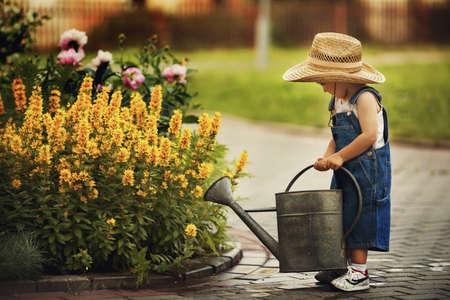 Foto de cute little boy watering flowers watering can - Imagen libre de derechos