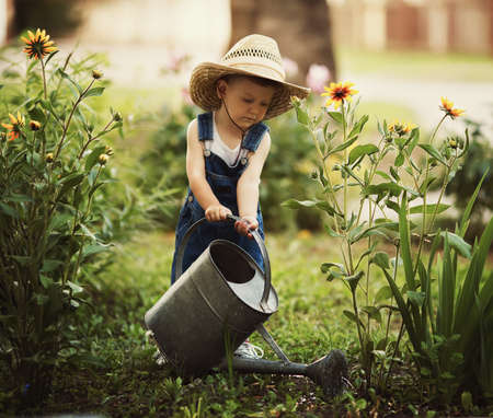 Foto de cute little boy watering flowers watering can - Imagen libre de derechos