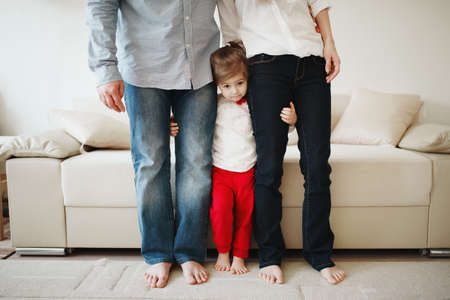 Photo for little girl hugging mom and dad for legs - Royalty Free Image