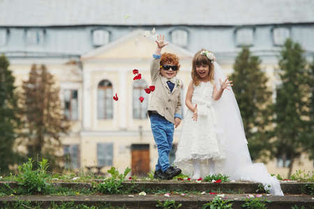 Photo pour Two funny little bride and groom - image libre de droit