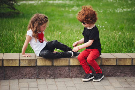 Photo pour boy helps little girl tie shoelaces - image libre de droit