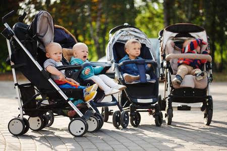 Foto de funny children sitting in strollers in park - Imagen libre de derechos