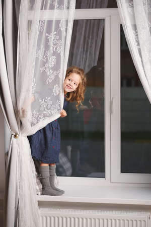 Photo for little girl on the windowsill at home - Royalty Free Image