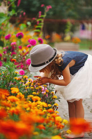 Foto de little beautiful girl in flowers park - Imagen libre de derechos