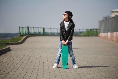 Photo pour little girl with skateboard on the street - image libre de droit