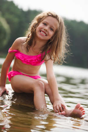 Foto per cute happy little girls in sumer lake - Immagine Royalty Free