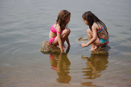 Photo pour cute happy little girls in sumer lake - image libre de droit